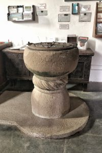 Font, Church of St Enodoc, a pretty church with a stone tower in the middle of a gold course, North Cornwall, England