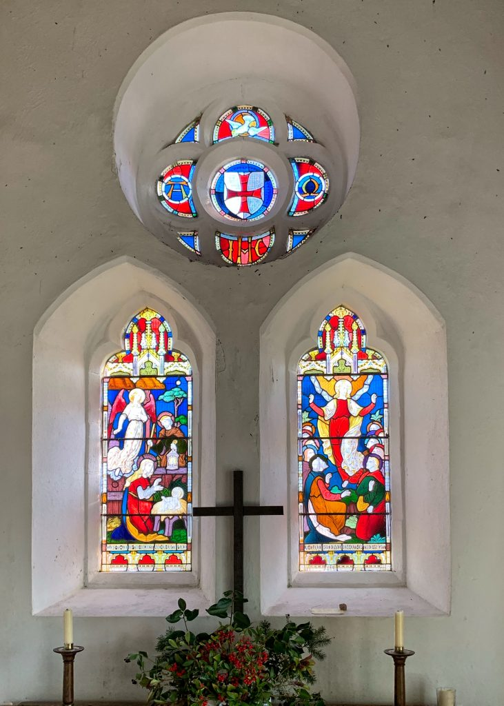 Stained glass windows above the altar containing Templar emblems at Temple Church, Bodmin Moor, Cornwall