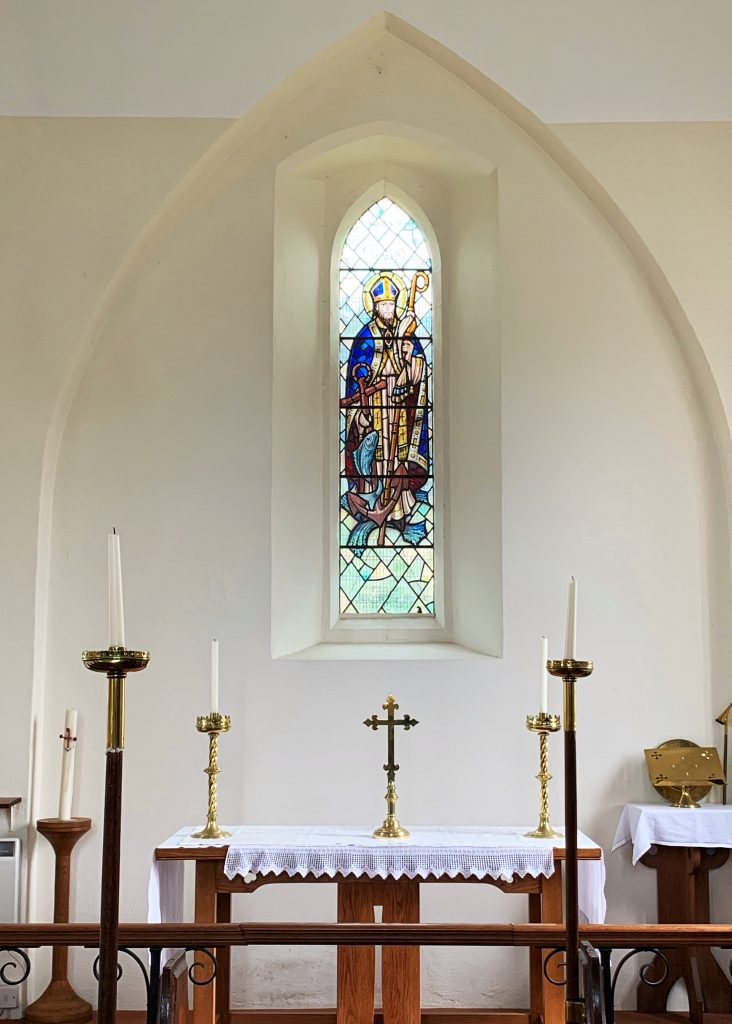 Altar with stained glass of St Clement above at the Church of St Clement, Hope Cove, South Hams, Devon