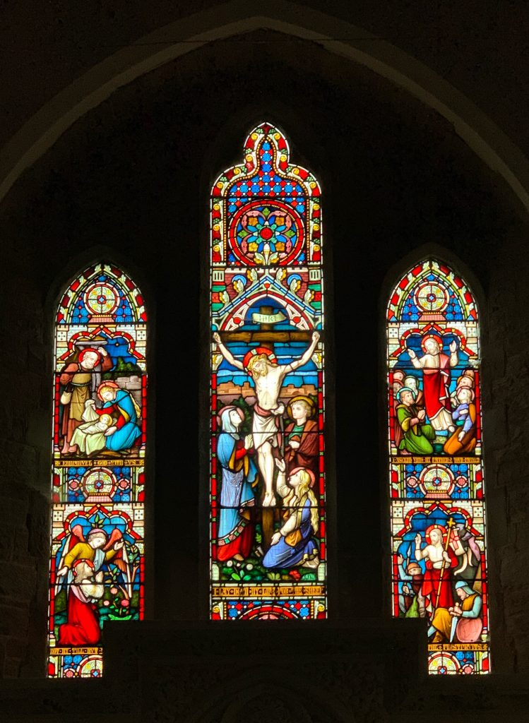 Stained glass of the crucifixion above the altar in the Church of the Holy Trinity, Galmpton, South Hams, Devon
