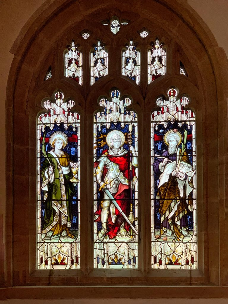 Stained glass window of St John, St George and St Barnabas by the stained glass studio of Hardman and Co. at the church of St Mary the Virgin, Compton Pauncefoot, Somerset