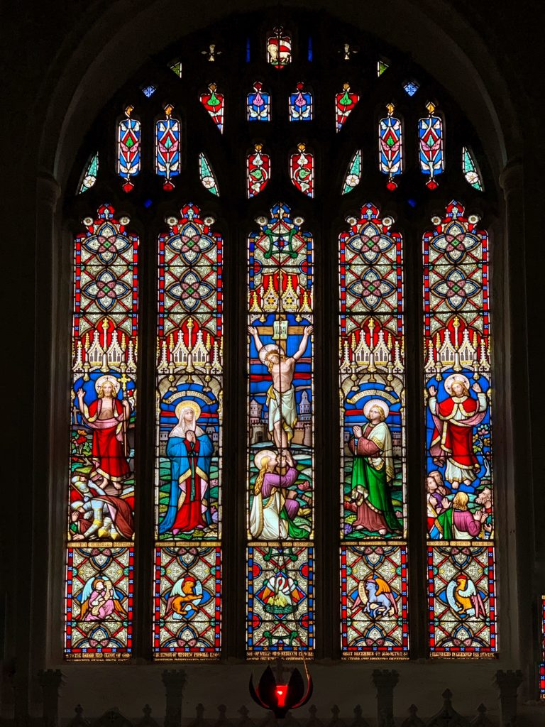 Stained glass window above the altar at the Churchof All Saints, Malborough, South Hams, Devon