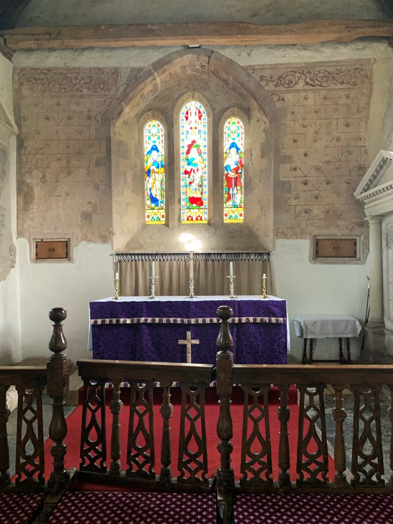The Altar with 17th century communion rail and early murals on the east wall at the Church of St Andrew, Great Durnford, Wiltshire.