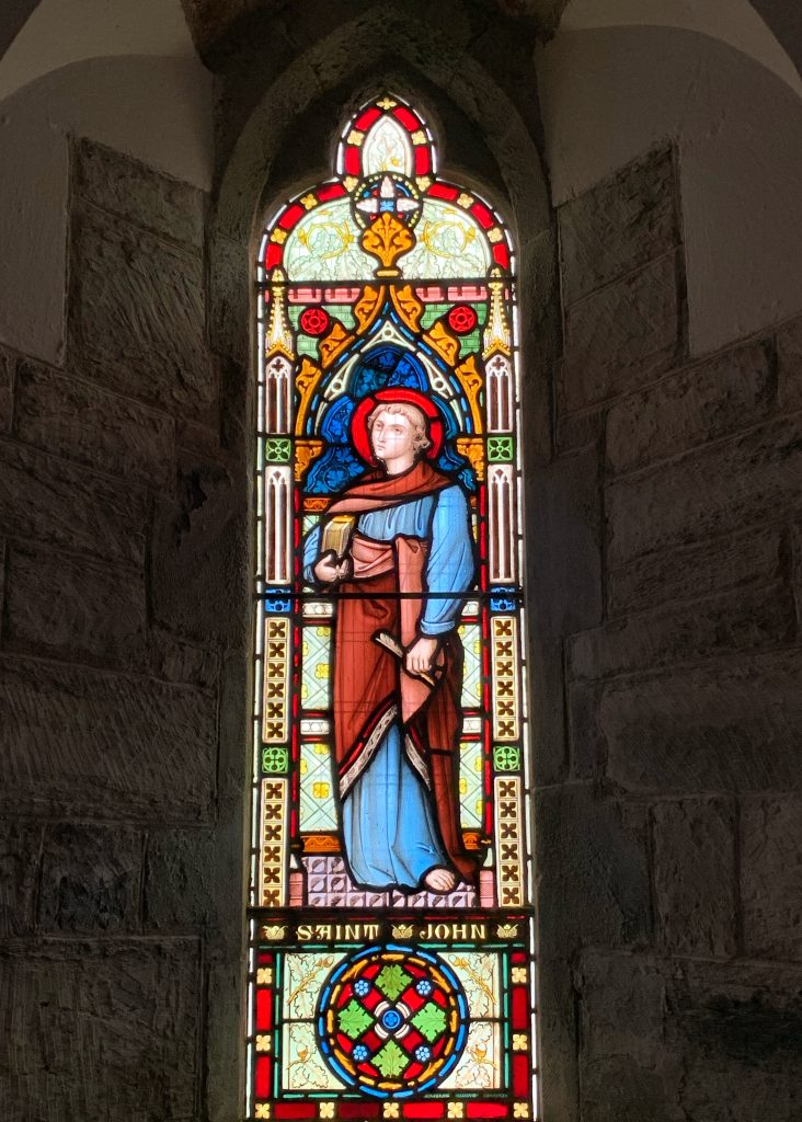 Stained glass window of St John at the Church of the Holy Trinity, Galmpton, South Hams, Devon